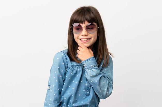 Mała dziewczynka z okulary na białym tle patrząc z boku i uśmiechnięty
