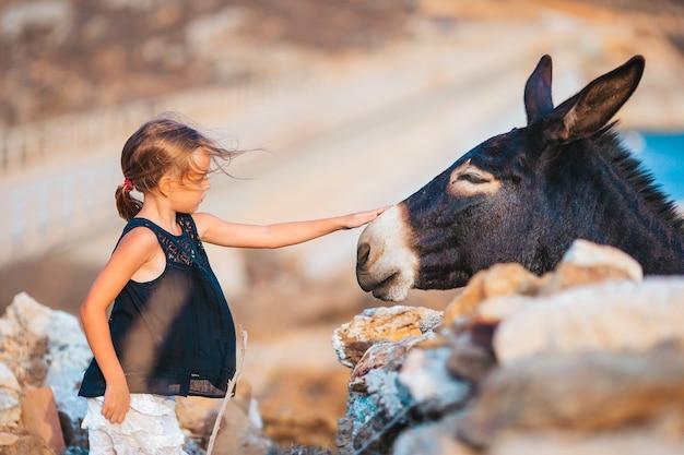 Mała dziewczynka z osłem na wyspie mykonos