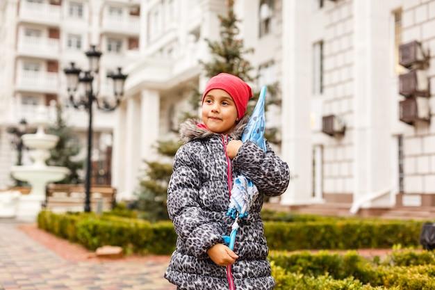 Mała dziewczynka z parasolem na ulicie w mieście