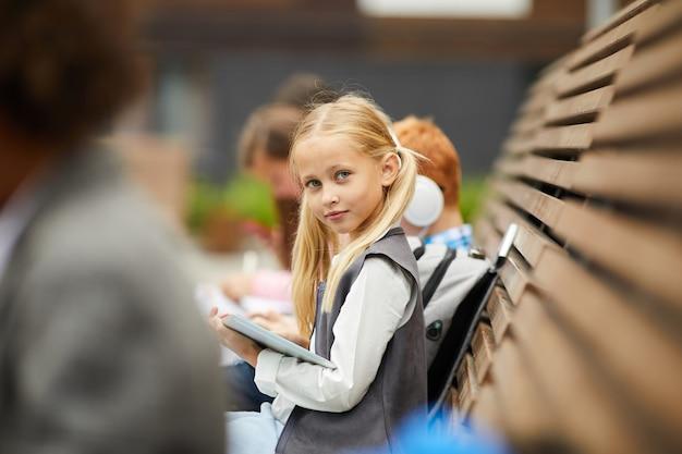 Mała dziewczynka z pastylka komputerem osobistym outdoors