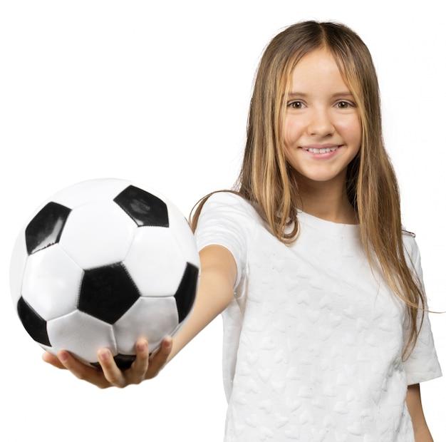 Mała dziewczynka z piłką nożną odizolowywającą na a nad białym tłem
