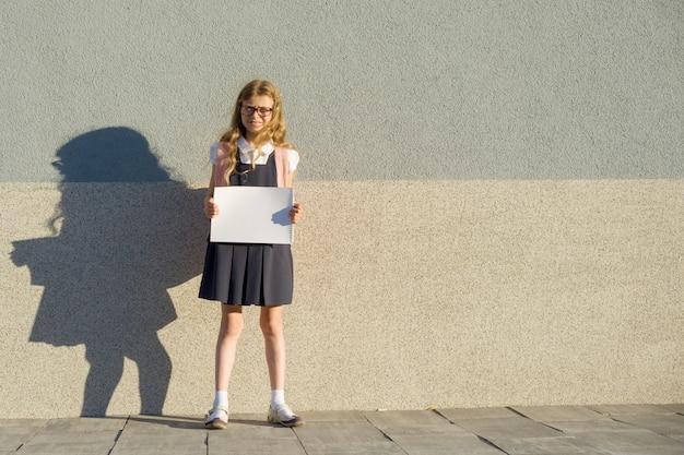 Mała dziewczynka z plecakiem pokazuje pustego białego prześcieradła plakat