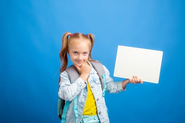 Mała dziewczynka z plecakiem trzyma kartkę pustego papieru na niebieskim tle
