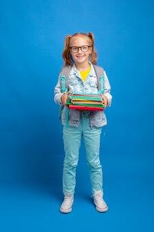 Mała dziewczynka z plecakiem trzyma książkę na niebieskim tle