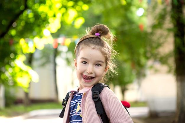 Mała dziewczynka z plecakiem wesoło wygląda i pokazuje język