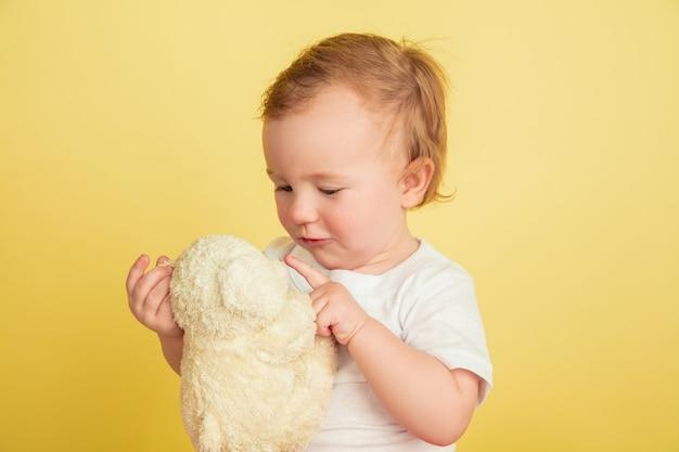Mała dziewczynka z pluszakiem na białym tle na żółtej ścianie studia