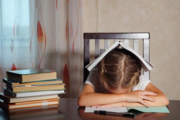 Mała dziewczynka z podręcznikami wygląda na zmęczoną i opiera się na rękach, siedząc przy stole i studiując