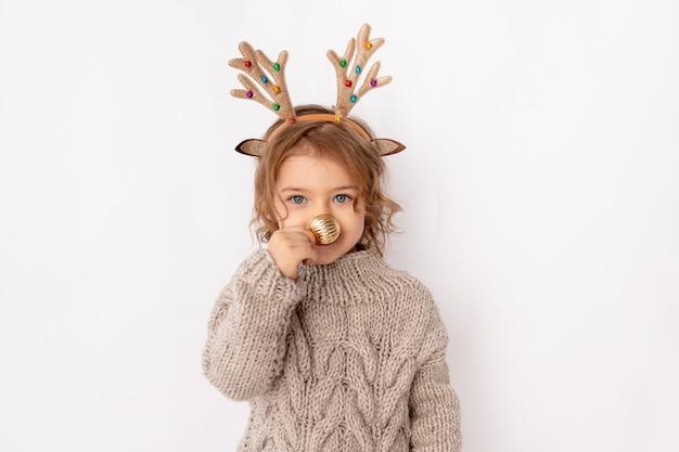 Mała dziewczynka z poroża jelenia i boże narodzenie piłka na nosie na białym tle, miejsca na tekst, koncepcja nowego roku i bożego narodzenia