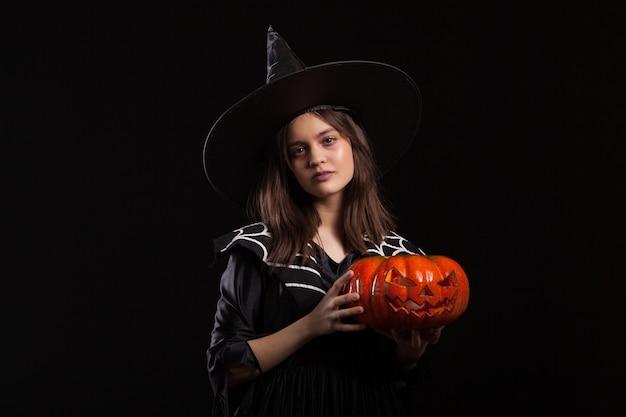 Mała dziewczynka z poważną miną, która rzuca zaklęcie, trzymając dynię na halloween. dziecko ubrane na karnawał na halloween.