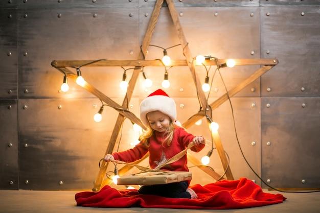 Mała dziewczynka z prezentami na boże narodzenie siedzi na czerwonej kocem przez gwiazdę