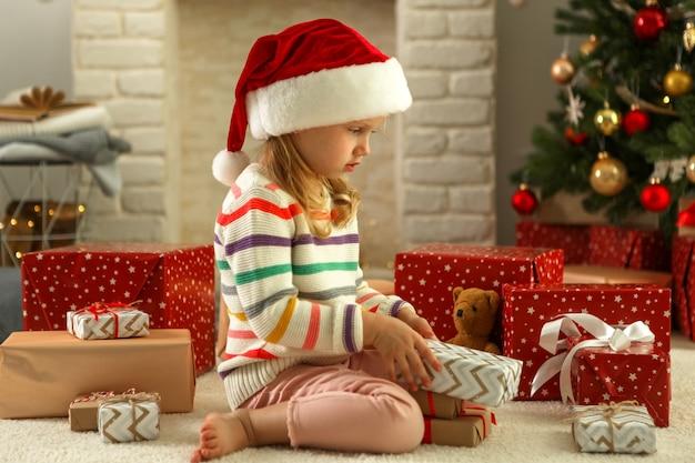Mała dziewczynka z prezentami świątecznymi w świątecznym wnętrzu