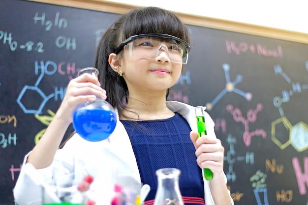 Mała dziewczynka z próbną tubką robi eksperymentowi przy szkolnym laboratorium. nauka i edukacja.