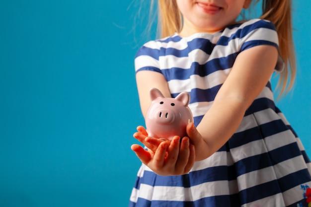 Mała dziewczynka z prosiątko banka moneybox przeciw błękitnemu tłu