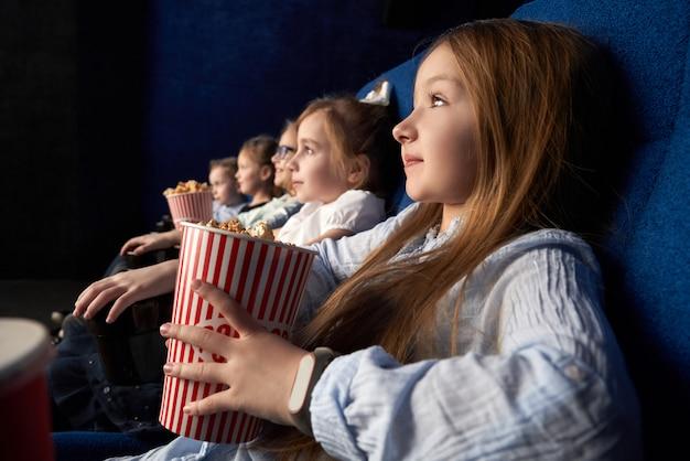 Mała dziewczynka z przyjaciółmi siedzi w kinie.