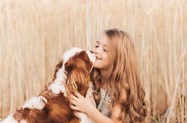 Mała dziewczynka z psem cavalier king charles spaniel bawi się latem na łonie natury