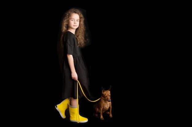Mała dziewczynka z psem, czarnym i żółtym ubraniem. czarne tło. strzelanie studyjne. koncepcja zwierząt domowych. szczęśliwe dzieciństwo. zdjęcie wysokiej jakości
