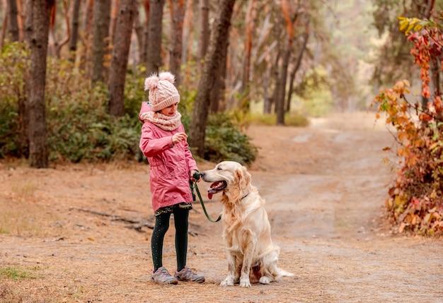 Mała dziewczynka z psem golden retriever ucieka w kolorowy jesienny las