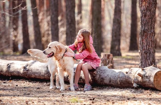 Mała dziewczynka z psem golden retriever w drewnie