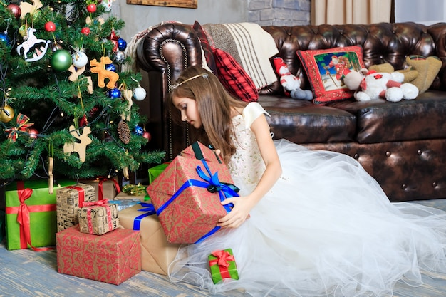 Mała dziewczynka z pudełkami prezentowymi w świątecznym wnętrzu