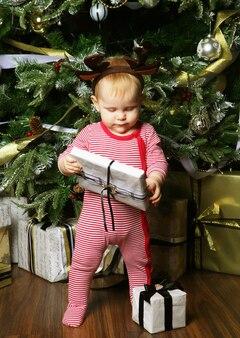 Mała dziewczynka z pudełkiem w pobliżu dekorowanie choinki. szczęśliwy czas.