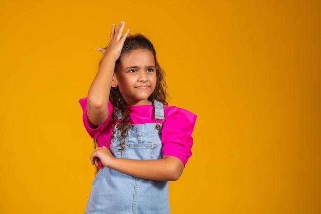 Mała dziewczynka z rękami na twarzy zapomina o czymś