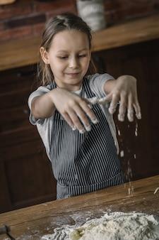 Mała dziewczynka z rękami w mące
