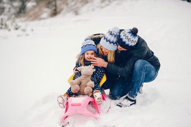 Mała dziewczynka z rodzicami bawić się w zima parku