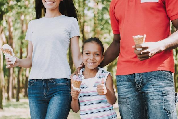 Mała dziewczynka z rodzicami je lody w lesie.