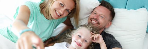 Mała Dziewczynka Z Rodzicami Leży Na łóżku Portret Premium Zdjęcia