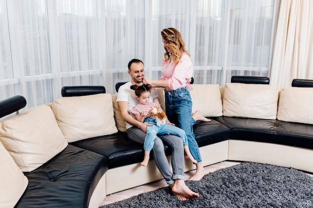 Mała dziewczynka z rodzicami w domu na kanapie. opieka nad dziećmi, macierzyństwo i ojcostwo.
