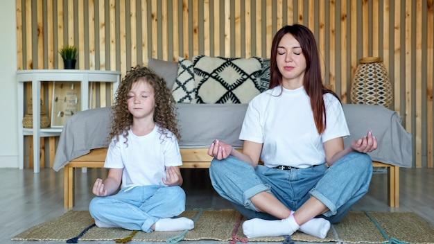 Mała dziewczynka z rozpuszczonymi włosami i matką siedzą w pozach jogi