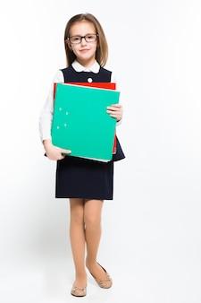 Mała dziewczynka z segregatorami w jej rękach ubierał jako bizneswoman