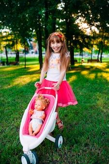 Mała dziewczynka z spacerowiczem w parku