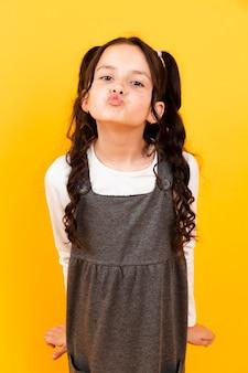 Mała dziewczynka z suknią robi buziak pozie