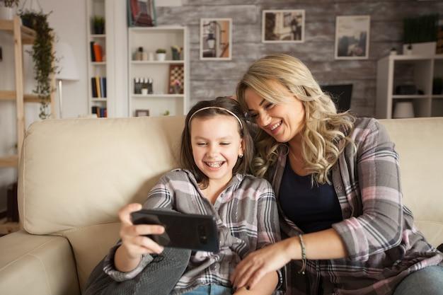 Mała dziewczynka z szelkami i jej matka zabawy relaksujący siedząc na kanapie za pomocą smartfona w salonie.