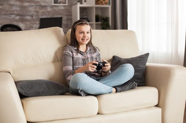 Mała dziewczynka z szelkami siedzi na kanapie, grając w gry wideo za pomocą bezprzewodowego kontrolera.