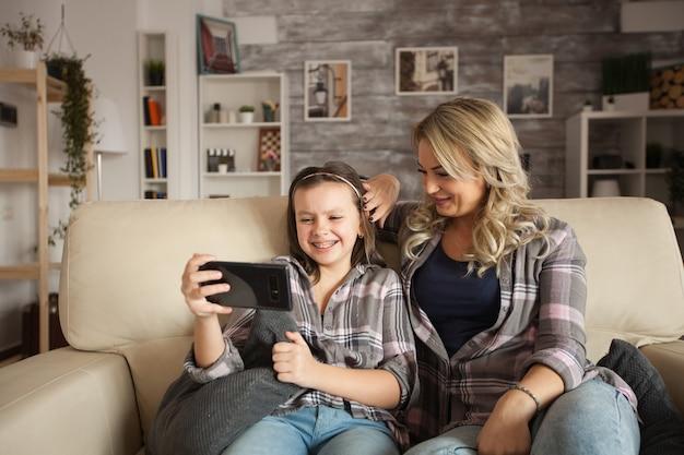 Mała dziewczynka z szelkami uśmiecha się podczas korzystania z aplikacji telefonu. matka spędza czas z córką.