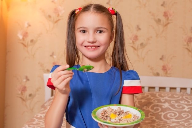 Mała dziewczynka z talerzem i łyżką w rękach.