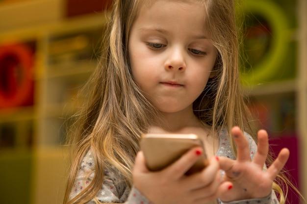 Mała Dziewczynka Z Telefonem Komórkowym Premium Zdjęcia