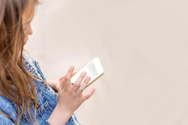 Mała dziewczynka z telefonem w dłoniach na ulicy latem. skopiuj miejsce na tekst