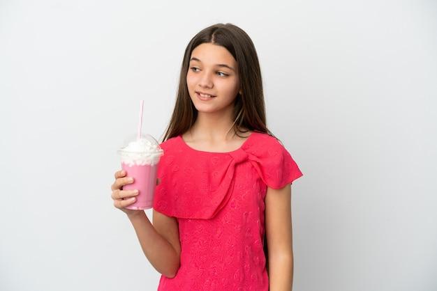 Mała dziewczynka z truskawkowym koktajlem mlecznym na białym tle, patrząc w bok i uśmiechając się