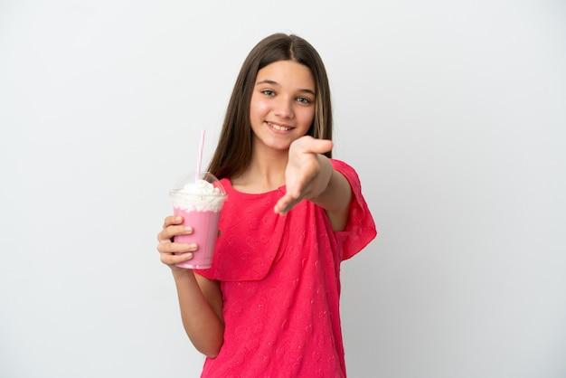Mała dziewczynka z truskawkowym koktajlem mlecznym na białym tle, ściskając ręce, aby zamknąć dobrą ofertę