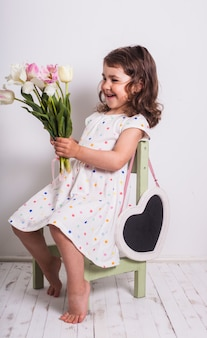 Mała dziewczynka z tulipanami i pudełkiem z prezentem dla mamy