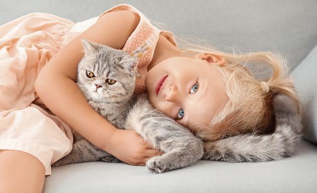 Mała dziewczynka z uroczym kotem w domu