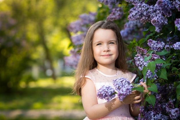 Mała dziewczynka z uśmiechem jest w krzakach bzu w ogrodzie o zachodzie słońca, kwitnącym wiosną.