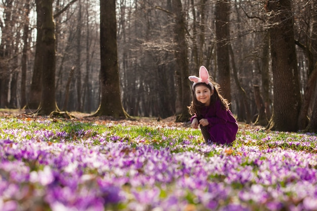 Mała dziewczynka z uszami bani wygląda zza drzewa w parku