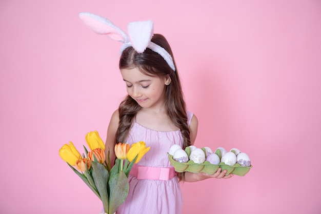 Mała dziewczynka z uszami easter bunny trzyma bukiet tulipanów i tacę z jajkami w dłoniach na różowej ścianie.