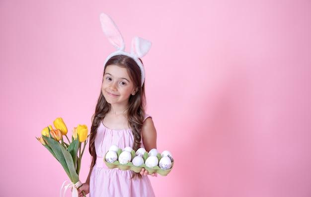Mała dziewczynka z uszami easter bunny trzyma bukiet tulipanów i tacę z jajkami w dłoniach na różowym tle studio.