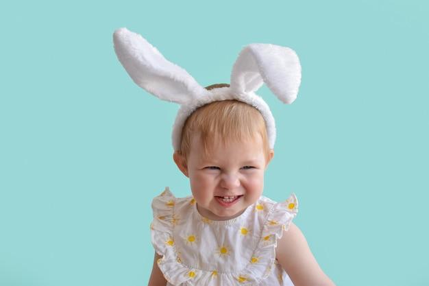 Mała dziewczynka z uszami królika wyszczerza zęby. tło wielkanoc.