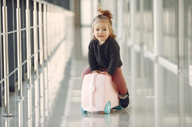Mała dziewczynka z walizką na lotnisku